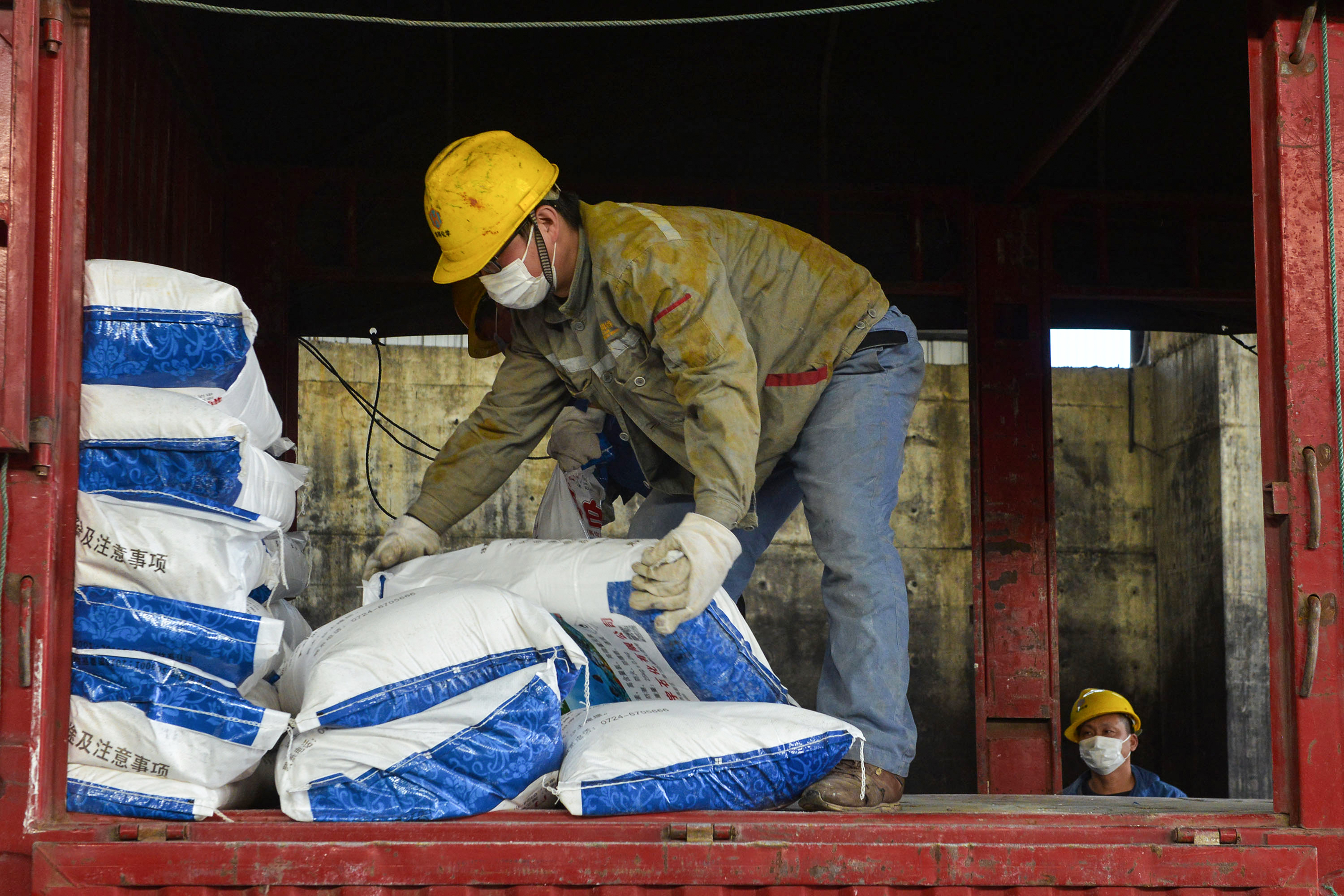 This photo taken on January 30, 2020 shows a worker transferring bags of disinfectant at a factory in Xiaogan in China's central Hubei province, to support the supply of medical materials during the virus outbreak in Hubei's city of Wuhan. - The nationwide death toll in China's coronavirus outbreak has risen to 213, with nearly 2,000 new cases confirmed, the National Health Commission said on January 31. (Photo by STR / AFP) / China OUT (Photo by STR/AFP via Getty Images)